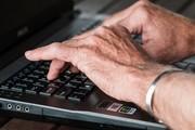 Das Bild zeigt Hände einer älteren Person auf der Tastatur eines Laptops.