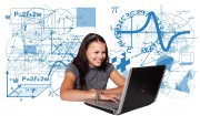 Das Symbolbild zeigt eine junge Frau an einem aufgeklappten Laptop, hinter der ganz viele mathematischen Gleichungen, Sprüche etc. auf der Wand stehen.