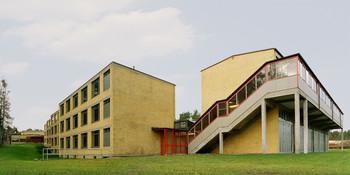 Bundesschule aus gelbem Klinker mit außenliegender verglaster Treppe