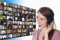 Das Bild zeigt eine junge Frau mit Headset, die vor einem Screen sitzt, auf dem ganz viele kleine Videobilder von Gesprächspartnern abgebildet sind.