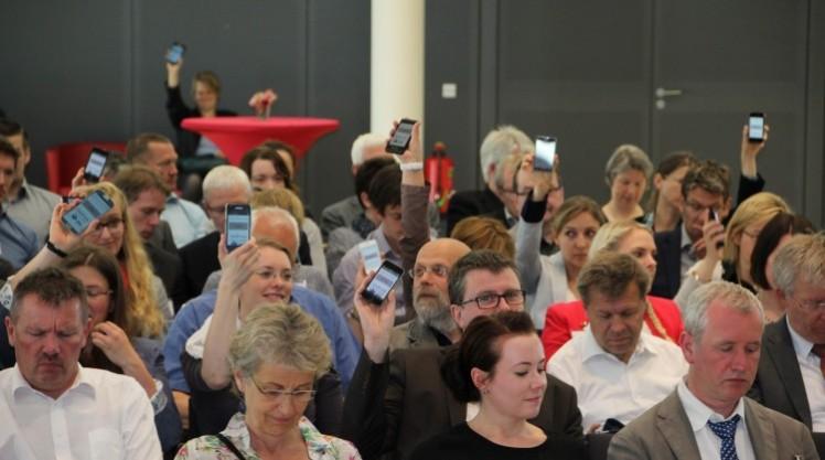 Teilnehmerinnen und Teilnehmer der IAG-Trainertage zeigen ihre Smartphones.