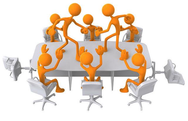 Gezeichnete Figuren sitzen um einen Tisch, zwei stehen sich auf dem Tisch gegenüber