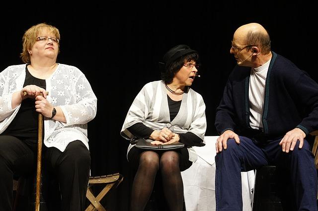 Zwei Frauen und ein Mann sitzen und unterhalten sich