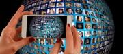 Das Bild zeigt zwei Hände mit einem Smartphone, die eine Weltkugel mit ganz vielen kleinen Videofenstern mit Menschen darauf aufnimmt.