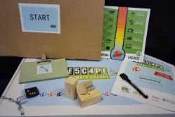"""Das Bild zeigt den Spielkarton der Spiels """"Escape Climate Change"""" mit einigen Materialien aus dem Spiel."""