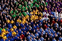 viele Menschen in farblich unterschiedlichen Hemden in Gruppen