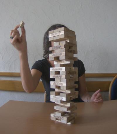 Eine Frau legt einen Stein auf einen Jenga-Turm. Der Turm ist bereits sehr hoch gebaut.