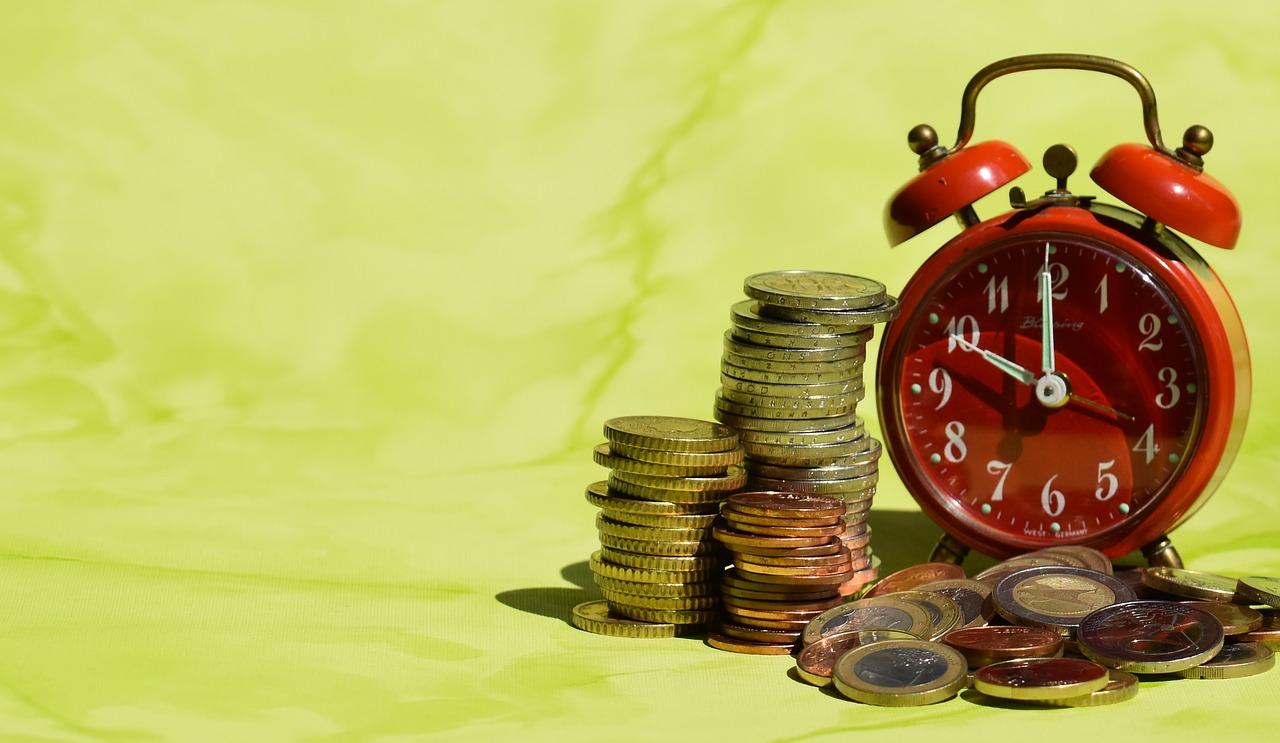 Das Bild zeigt eine Uhr und kleine Münzstapel.
