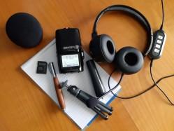 Das Bild zeigt ein Foto einer Podcastausstattung mit einem Mikrophon, einem Tischstativ, einem Paar Kopfhörere, einem Schreibblock, einem Windschutz und einer Speicherkarte.
