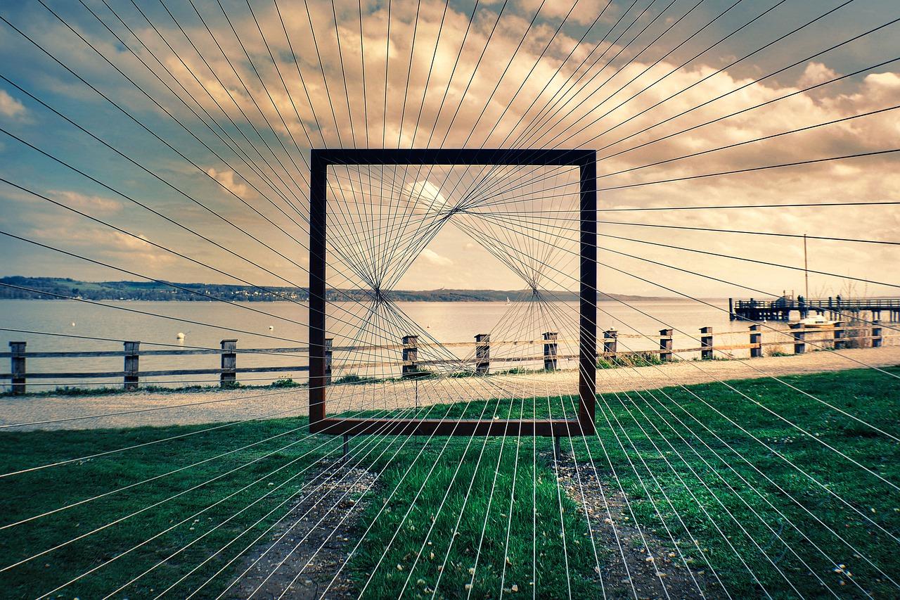 """Das Bild zeigt ein Seilkunstwerk """"Blickfang"""" mit Blick auf einen See."""