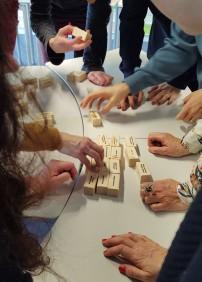 Das Bild zeigt mehrere Personen, die um einen Tisch herumstehen und auf kleine Holzklötze weisen, die auf dem Tisch verteilt liegen.