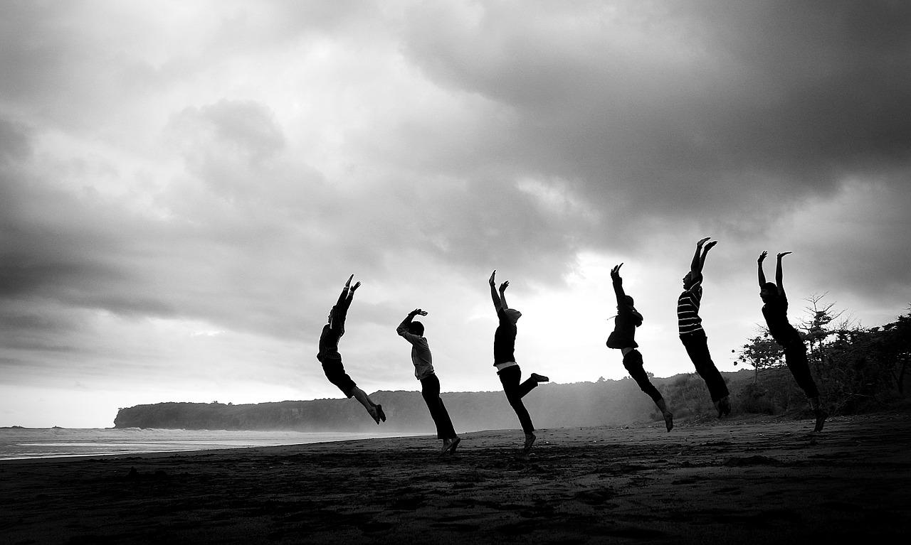Das Bild zeigt Menschen die am Strand hochspringen.