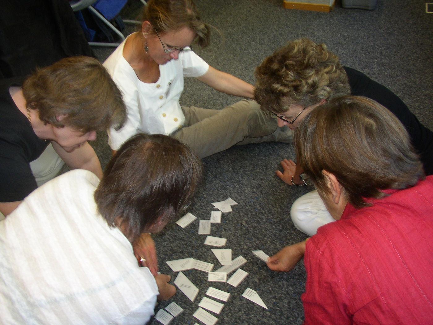 5 Frauen sitzen auf dem Boden und sortieren Kärtchen