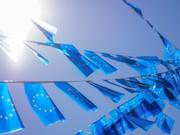 Das Bild zeigt zahlreiche blaue Europafahnen, die an Seilen vor blauem Himmel aufgereiht im Wind wehen.