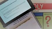 Das Bild zeigt ein Tablet mit dem Grundgesetz, dem Spiel Monopoly und einem Notizblock mit Stift