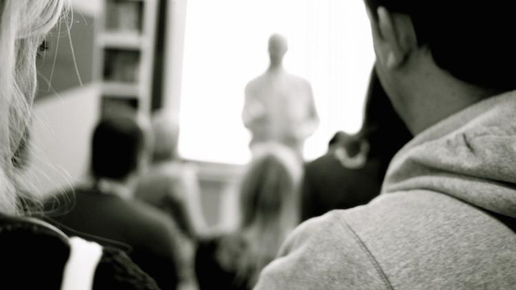 Publikum schaut auf Leinwand und Vortragenden