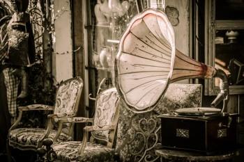 Lautsprecher eines alten Grammophons vor alten Möbeln