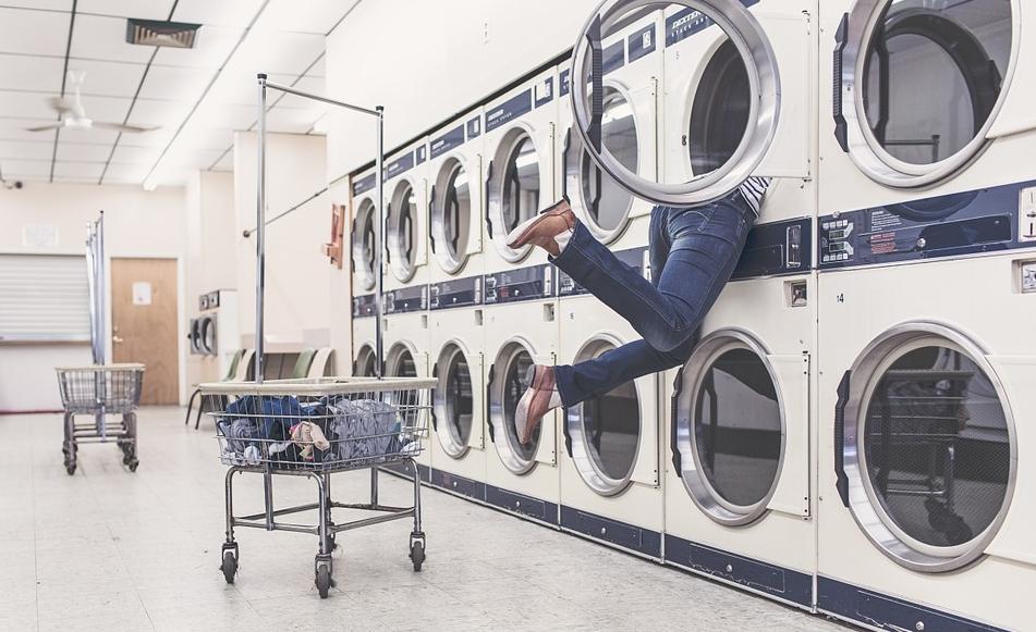 Eine Person steckt halb in einer Waschmaschine fest und die Beine baumeln raus.