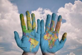 Hände mit aufgemalter Landkarte vor Wolken und Himmel