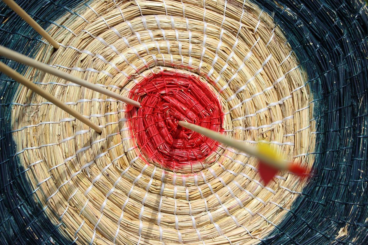 Zielscheibe mit rotem Zentrum, vier Pfeile stecken darin.