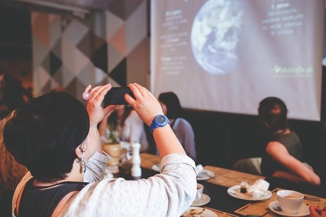 Eine Frau sitzt mit anderen Frauen an einem Tisch und fotografiert mit ihrem Handy etwas das mit einem Beamer an die Wand geworfen wird