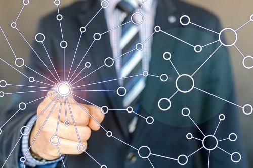 Mann im Anzug hinter einem gezeichneten Netz zwischen Kreisen. Klickt  mit dem Zeigefingern einen an.
