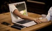 Das Bild zeigt einen aufgeklappt Laptop, aus dessen Bildschirm eine Hand herausgreift und die reale Hand des Laptopnutzers schüttelt.