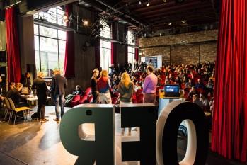 Großbuchstaben auf einer Bühne im Vordergrund, dahinter Publikum