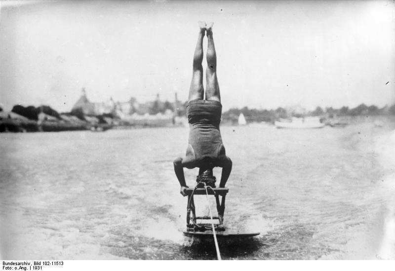 Mensch steht Kopf auf einem Hocker, der auf einem Surfbrett hinter einem Boot hergezogen wird.