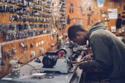 Das Bild zeigt einen jungen Mann bei der Arbeit in einem Schlüsseldienst.