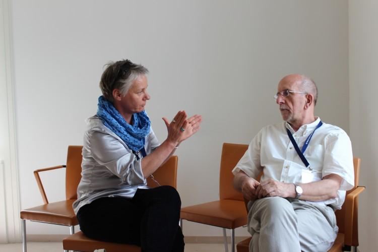 zwei Menschen sitzen sich gegenüber und einer redet.