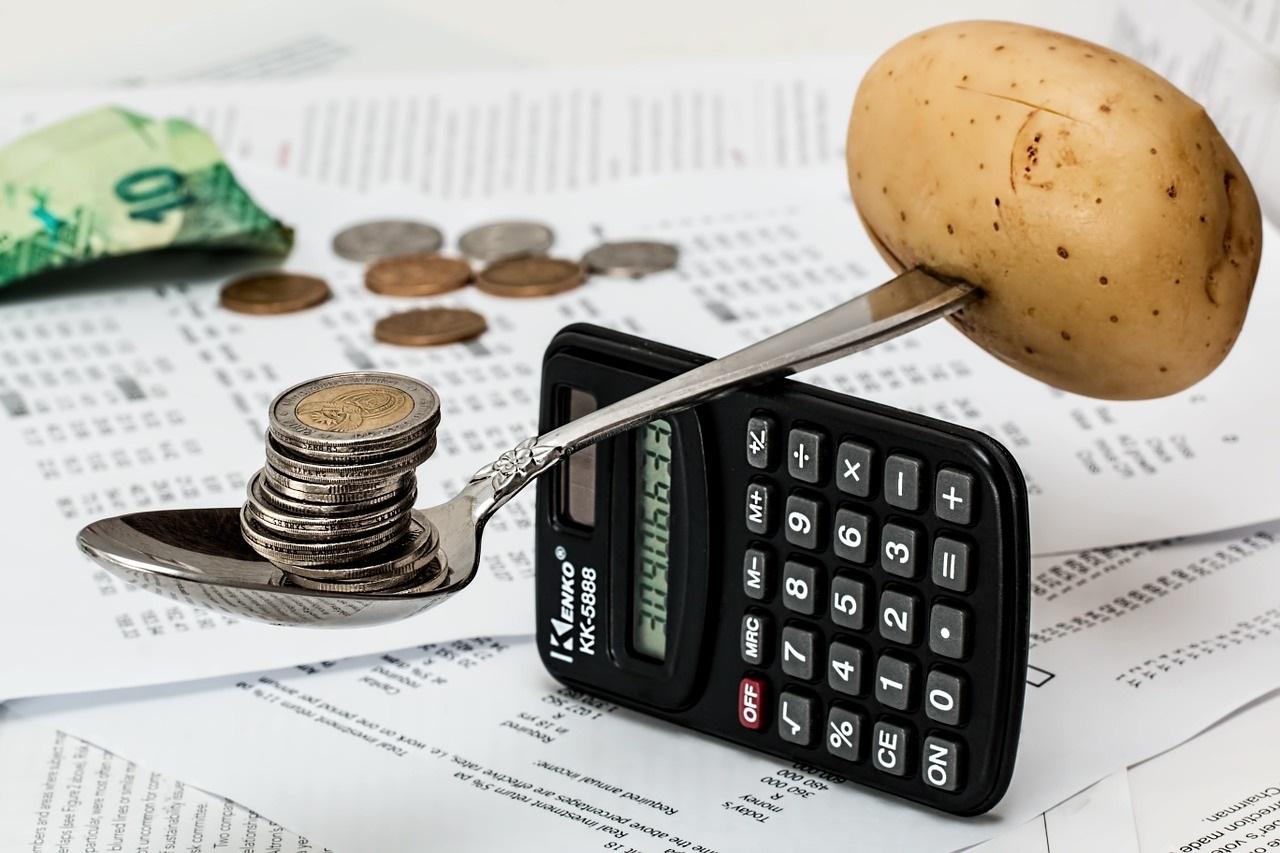 Ein Löffel balanciert eine Kartoffel gegen Münzen auf einem Taschenrechner aus.