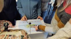 Das Bild zeigt mehrere Personen, die um einen Spielekarton herumstehen, der mit Kette und Schloss gesichert ist.
