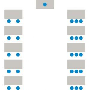 Tische stehen in Reihen hintereinander, alle Teilnehmer blicken zum Lehrenden-Pult.