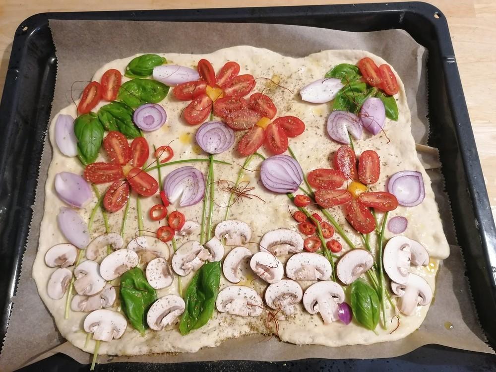 Das Bild zeigt eine Pizza, deren Zutaten als Blumenwiese arrangiert sind.