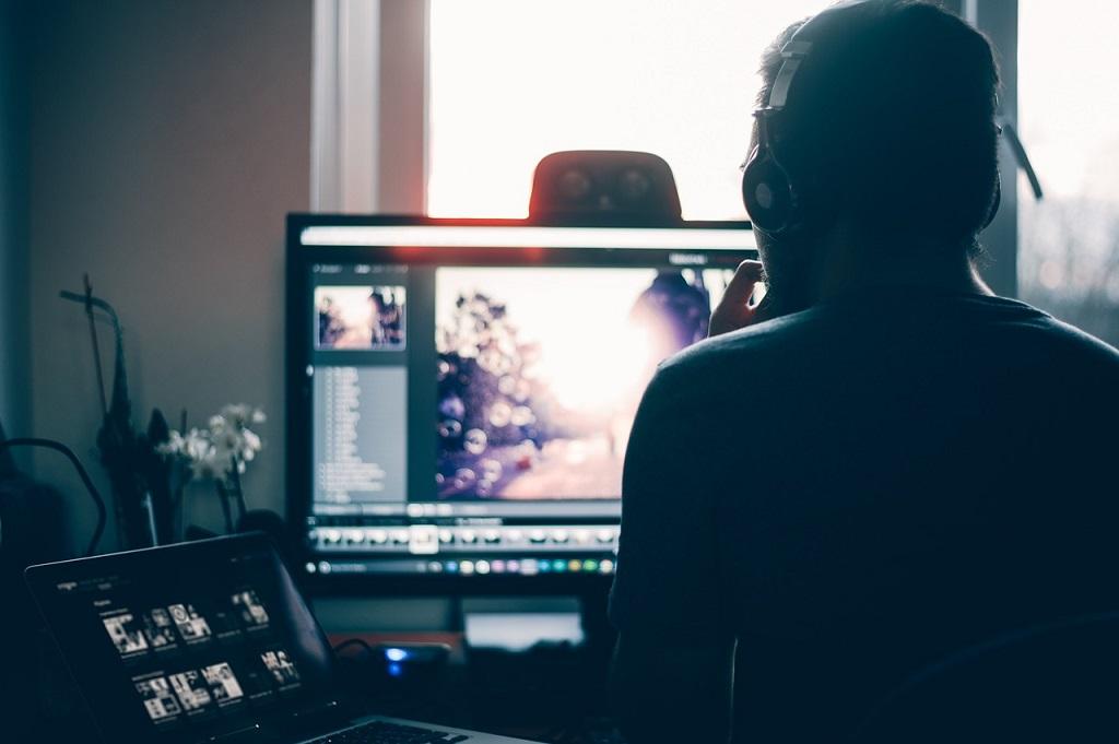 Das Bild zeigt einen Mann vor zwei Bildschirmen.