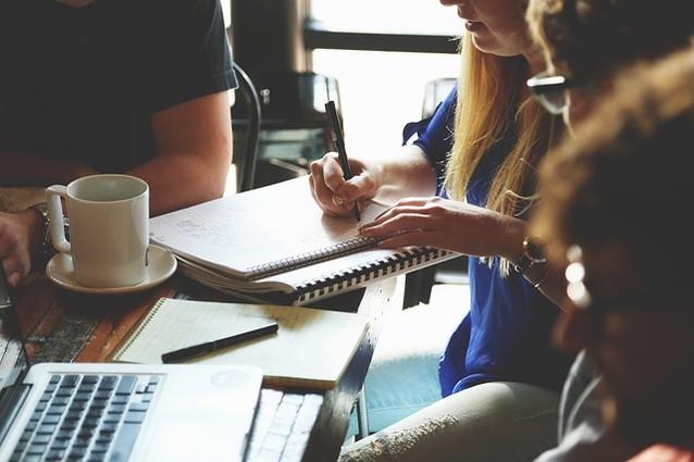 Mehrere Menschen sitzen um einen Holztisch, haben Notizen auf dem Tisch, einen Laptop und eine Kaffeetasse