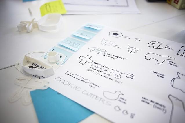 Auf einem Tisch liegen ein Blatt mit Zeichnungen und Zeichenschablonen.