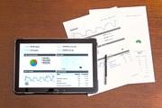 Das Bild zeigt Statistiken auf Tablet und Papier.