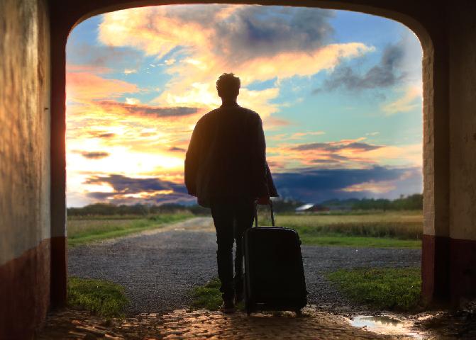 Ein Mann mit einem Koffer verlässt ein Haus im Sonnenuntergang.