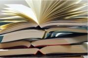 Das Bild zeigt einen Stapel aufgeschlagener Bücher.