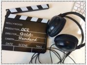 Das Bild zeigt eine Regieklappe und ein Paar Kopfhörer. Auf der Regieklappe steht der Schriftzug OER Gold-Standard.