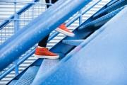 Das Bild zeigt die Füße einer Person, die die Treppe hochsteigt.