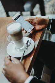 Das Bild zeigt einen Kaffee und daneben eine Hand mit einem Smartphone.