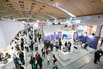 Blick in eine Ausstellungshalle mit Besuchern und Ständen