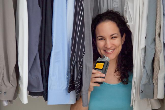 Die Podcasterin Annik Rubens mit ihrem Mikrofon im Kleiderschrank.