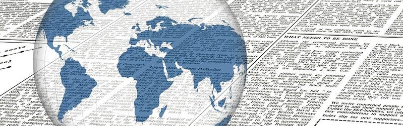 Das Bild zeigt eine Weltkugel, vor einer Zeitungsseite.