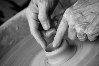 Hände an einem Werkstück auf einer Töpferscheibe