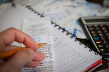 Hand mit Bleistift vor Kassenzettel, Rechenheft, Taschenrechner