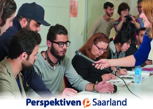 Kursteilnehmende sitzen um einen Tisch herum und eine Frau hält einem Mann ein Mikrofon vor den Mund. Unterhalb des Bildes steht Perspektiven Saarland